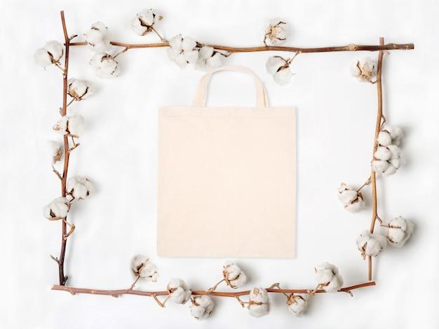 Flache lage der leeren stofftasche mit baumwollblumenzweigen auf weißem hintergrund