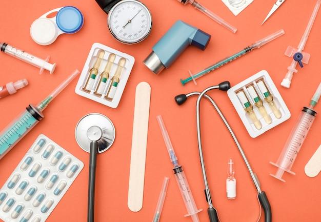 Flache lage der medizinischen werkzeuge auf farbigem hintergrund