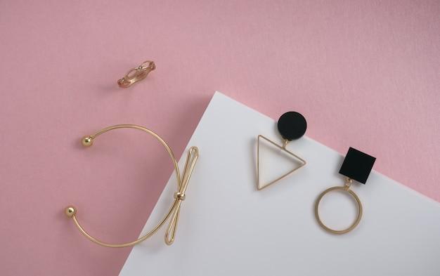 Flache lage der modernen goldenen accessoires der geometrischen formen auf rosa und weißer papieroberfläche