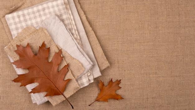 Flache lage der monochromatischen auswahl von textilien mit blättern