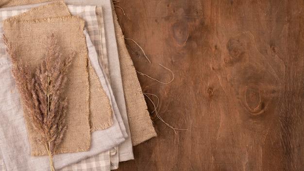 Flache lage der monochromatischen auswahl von textilien mit getrocknetem gras und kopierraum