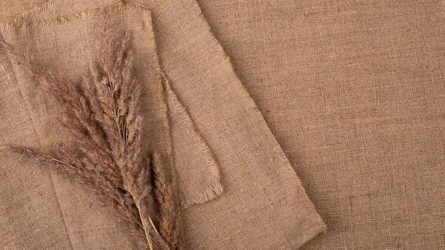 Flache lage der monochromatischen auswahl von textilien mit kopierraum und getrocknetem gras