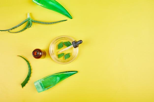 Flache lage der natürlichen zutaten der hausgemachten hautpflege pflanzen aloe vera gel, skinimalismus, langsame schönheit auf gelbem hintergrund, kopienraum.