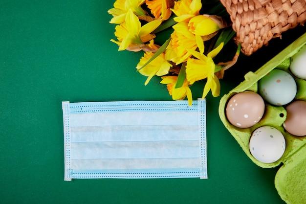 Flache lage der osterkomposition in der coronavirus-quarantäne. ostersymbol eier und narzissenblüten im korb nahe medizinischen schutzmasken,