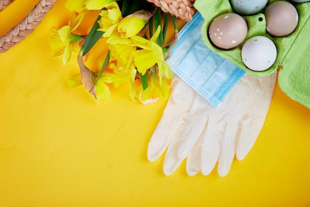 Flache lage der osterkomposition in der coronavirus-quarantäne. ostersymbol eier und narzissenblumen im korb nahe medizinischen schutzmasken und handschuhen