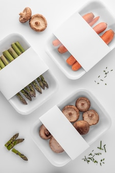 Flache lage der plastikverpackung mit pilzen, spargel und karotten