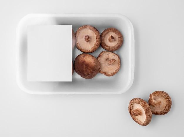 Flache lage der plastikverpackung mit pilzen