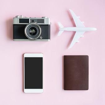 Flache lage der reiseartikel auf rosa schreibtisch.