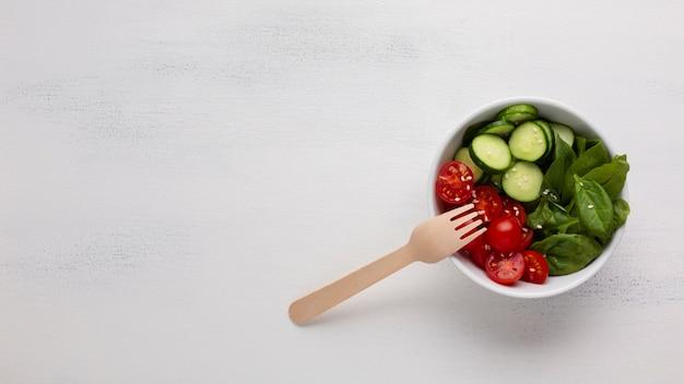 Flache lage der salatschüssel auf weißem hintergrund