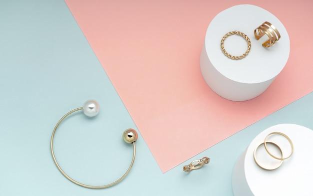 Flache lage der sammlung des goldenen und perlenarmbands und der goldenen ringe auf hintergrund des rosa und grünbuches