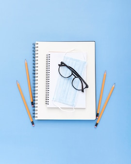 Flache lage der schulsachen mit brille und gesichtsmaske
