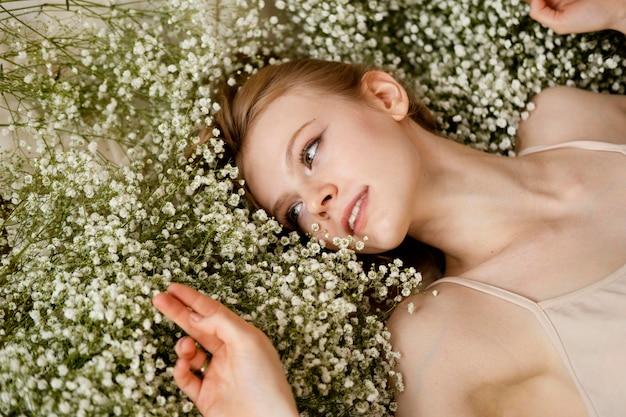 Flache lage der smiley-frau, die mit frühlingsblumen aufwirft