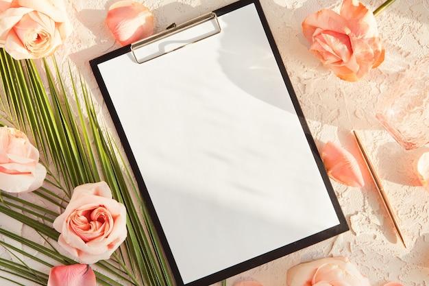 Flache lage der stilvollen zusammensetzung mit tropischem palmblatt, rosarosenblumen, auf pastell mit schatten und sonnenlicht