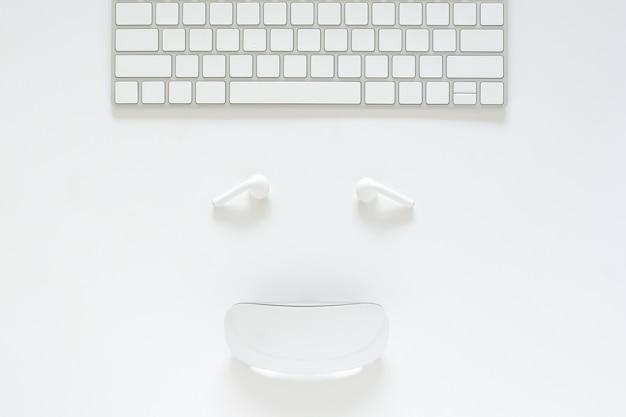 Flache lage der tastatur, des kopfhörers und der maus stellte als lächelndes gesicht auf weißem hintergrund für online-verkaufskonzept cyber montags ein.