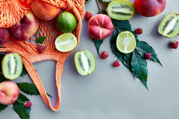 Flache lage der umweltfreundlichen mesh-einkaufstasche mit früchten himbeere, pfirsich, kiwi, limette auf grauer oberfläche im sonnenlicht, sommerzeit. lebensmittelkonzept, kopienraum, draufsicht.