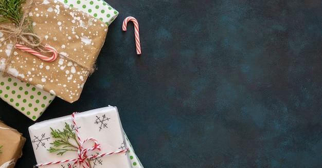 Flache lage der weihnachtsgeschenke mit zuckerstange und kopierraum