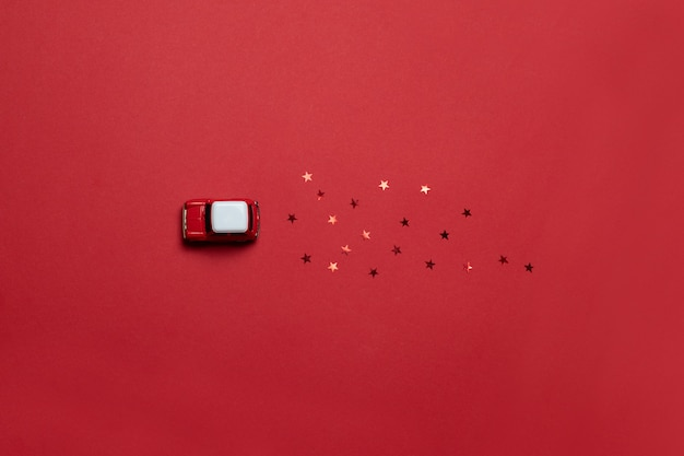 Flache lage der weihnachtszusammensetzung von karten mit einem roten modell eines kinderautospielzeugs mit funkelnsüßigkeit auf einem rot gesättigten hintergrund