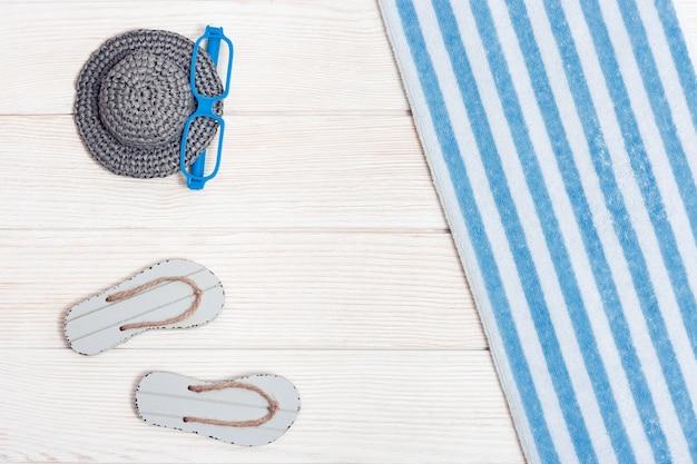 Flache lage der zusammengesetzten miniatur des strandloungebereichs mit sommerschuhen hut handtuch sonnenbrille