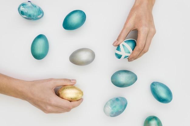 Flache lage der zusammenstellung der gemalten eier für ostern mit den händen