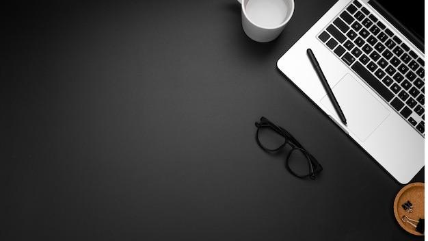 Flache lage des arbeitsplatzes mit kopienraum und -laptop