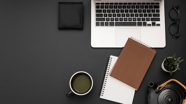 Flache lage des arbeitsplatzes mit laptop und tasse tee
