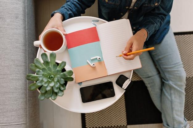 Flache lage des arbeitstisches mit der hand der jungen frau, die ein notizbuch mit einer smartphone-tasse tee und einer grünen pflanze schreibt