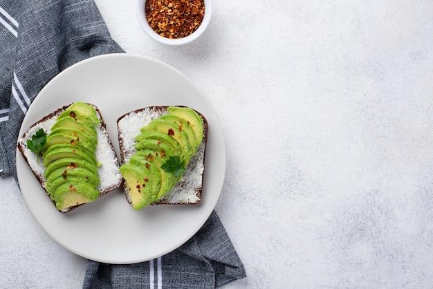 Flache lage des avocadotoasts auf platte mit kräutern und gewürzen
