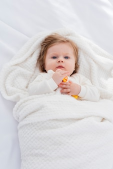 Flache lage des babys in der weißen decke
