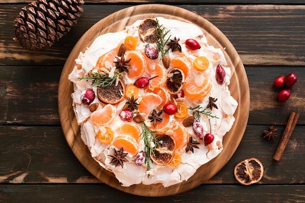 Flache lage des baiserkuchens mit zimt und zitrusfrüchten