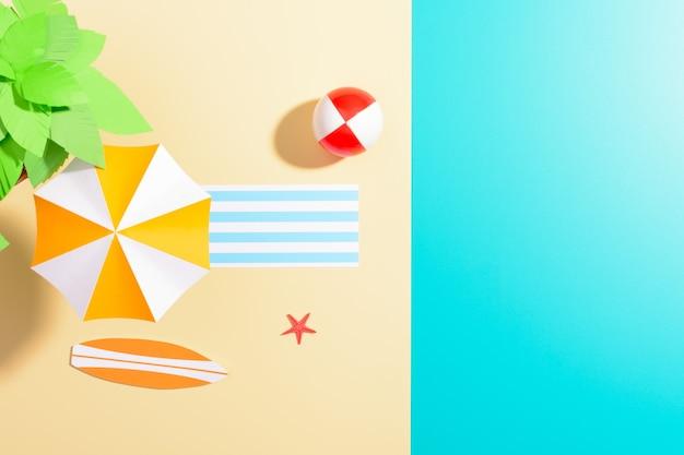 Flache lage des bunten regenschirms am strand mit grünem baum und unterhaltsamem gegenstand auf mehrfarbiger oberfläche.