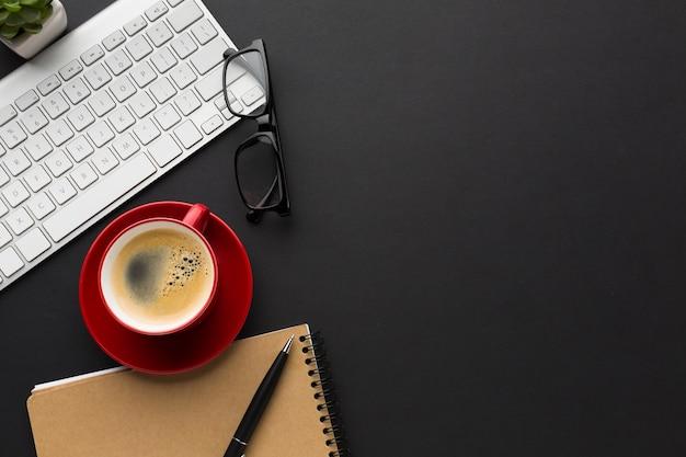 Flache lage des desktops mit kaffeetasse und notizbuch