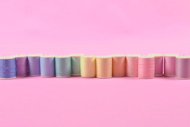 Flache lage des farbigen gewindes rollt für das nähen auf rosa hintergrund