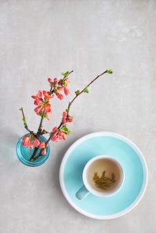 Flache lage des frühjahrs, tasse grüner tee und blumen der japanischen quitte auf einem grauen stein, kopieraum