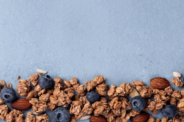 Flache lage des frühstückskost aus getreide mit blaubeeren und kopienraum