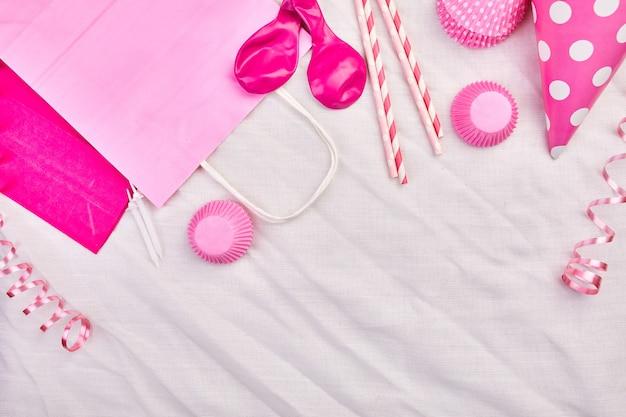 Flache lage des geburtstagskindes, draufsicht und kopierraum für text, rahmen oder hintergrund mit rosa festivalgegenständen, partyhüte und luftschlangen, geburtstags- oder partygrußkarte