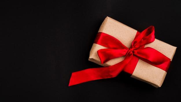 Flache lage des geschenks auf schwarzem hintergrund