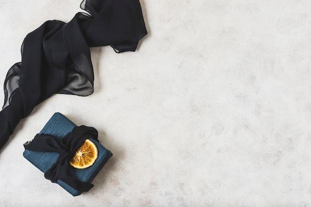 Flache lage des geschenks mit zitrusfruchtscheibe und kopienraum