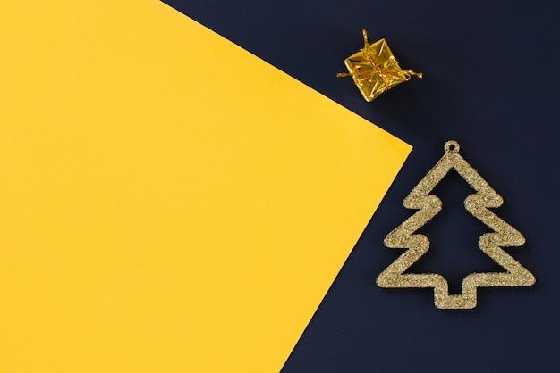 Flache lage des grußkartenplans, draufsicht. goldener weihnachtsbaum und geschenk auf dem hintergrund des mehrfarbigen blauen, gelben hintergrundes. grußkarten-layout-vorlage oder ihr text-design. kopieren sie platz