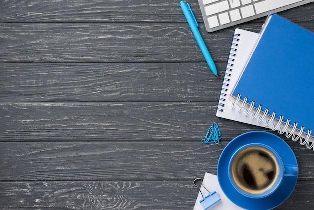 Flache lage des hölzernen schreibtisches mit notizbüchern und kaffeetasse mit kopienraum