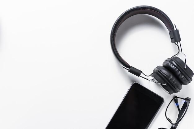 Flache lage des kopfhörers und des handys auf weißem hintergrund, musikkonzept