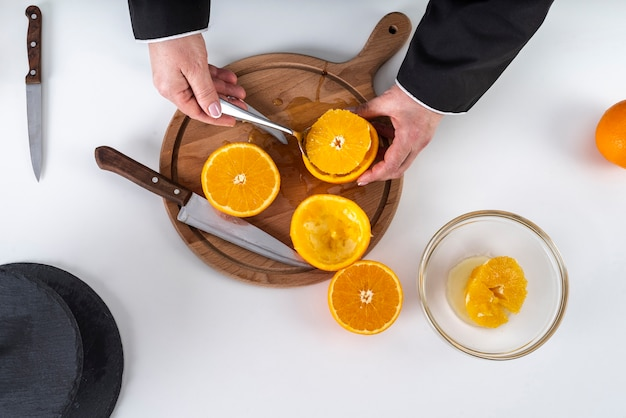 Flache lage des küchenchefs, der eine orange schneidet