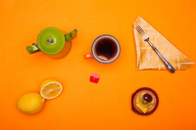 Flache lage des ländlichen frühstücks. draufsicht der weinlese-teetasse und der teetasse mit zitrone und gebäck