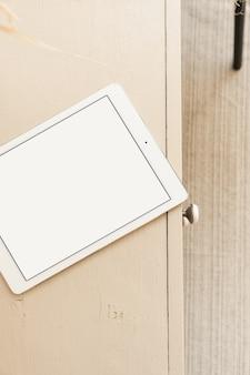 Flache lage des leeren bildschirmtabletts mit kopienraum auf pastellbeigem tisch. flache lage, draufsicht