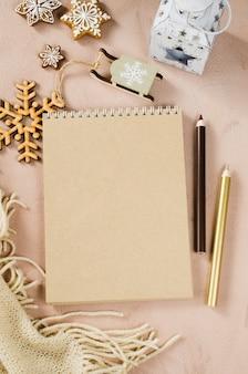 Flache lage des leeren braunen notizbuches mit weihnachtsdekoration und -plaid.