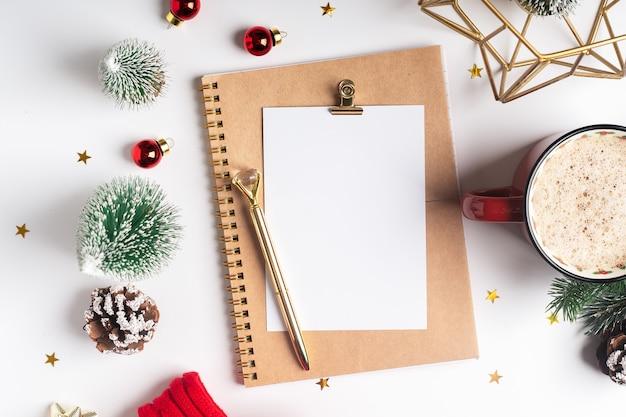Flache lage des leeren planers mit tasse kaffee und weihnachtsdekoration.