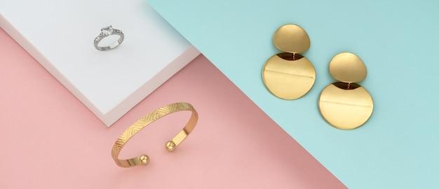 Flache lage des modernen goldenen schmucks auf pastellfarbenpapier