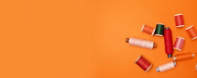 Flache lage des nähens farbiger fäden auf einem orangefarbenen hintergrund