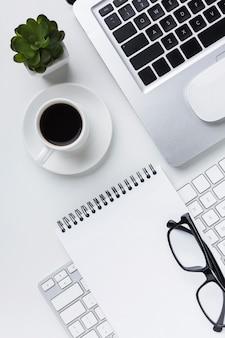 Flache lage des notizbuches mit gläsern und laptop auf schreibtisch