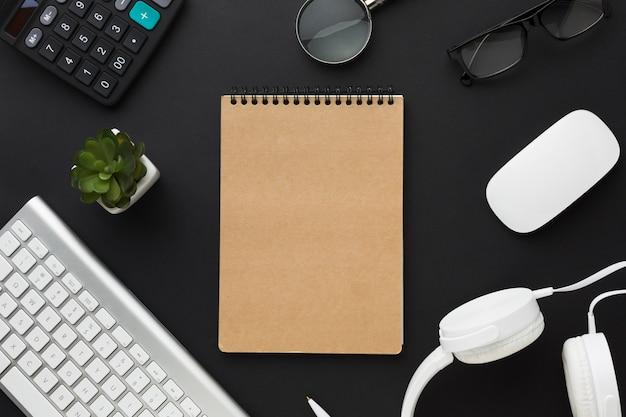 Flache lage des notizbuches mit tastatur auf dem desktop