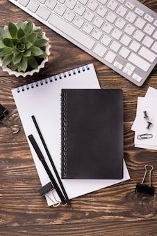 Flache lage des notizbuches und der tastatur auf hölzernem schreibtisch mit succulent